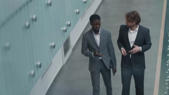 Two Male Colleagues Going along Office Hall and Talking