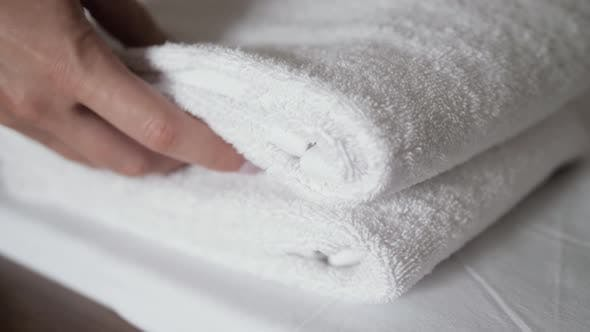Thumbnail for Close-up of Hands Putting Stack of Fresh White Bath Towels on the Bed Sheet. Room Service Maid