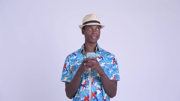 Thumbnail for Young Happy African Tourist Man Thinking While Using Phone