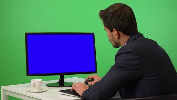 Thumbnail for A Young Businessman Sits at a Desk and Works on a Desktop Computer - Green Screen Studio