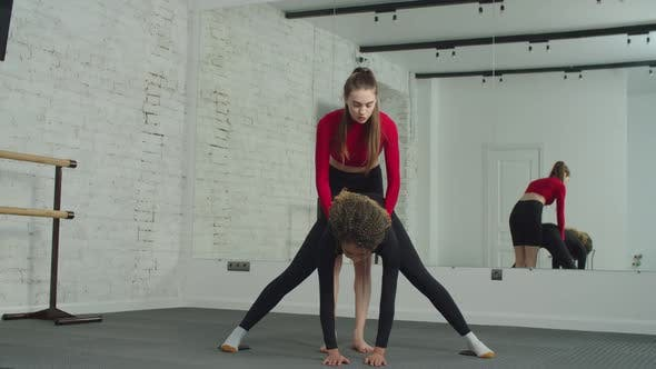 Personal Trainer Supporting Woman in Hamstring Muscles Stretch