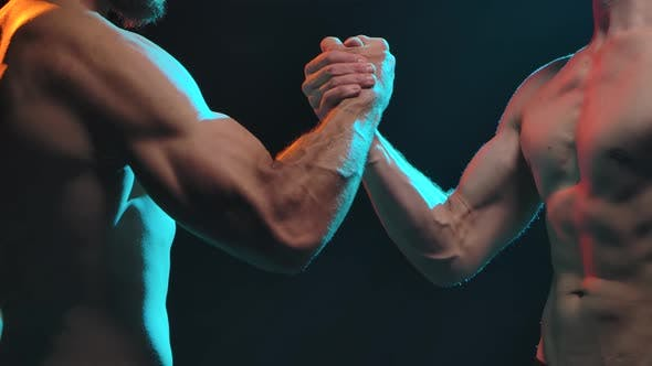 Thumbnail for Two Muscular, Naked-chested Men Shake Hands. Shot in the Studio on a Black Background. Slow Motion