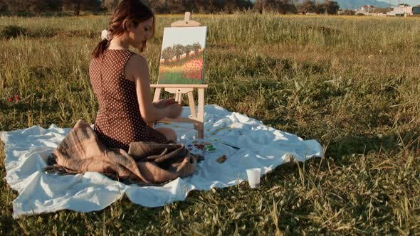 Happy girl painting outdoors