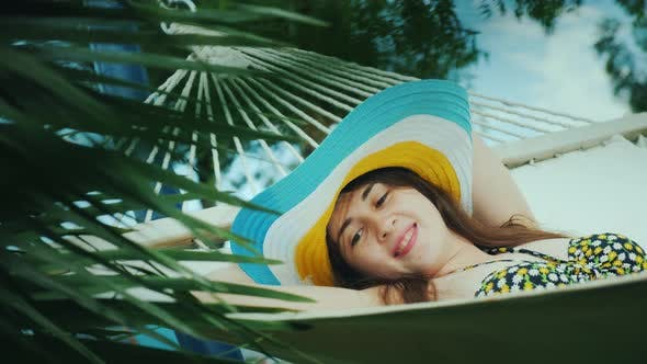 Thumbnail for A Pensive Young Girl Relaxes on a Hammock, Mysteriously Smiles