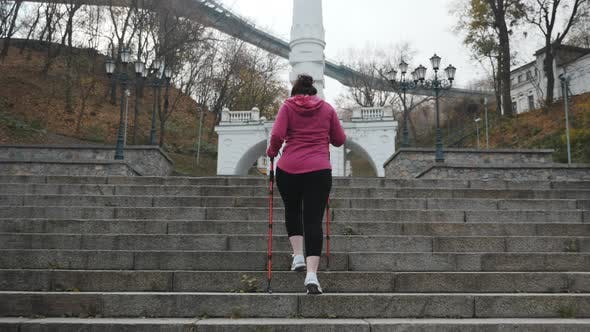 Thumbnail for Nordic Walking. Young adult doing nordic walking exercises in city going up the stairs