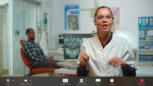 Stomatologist Doctor Talking on Web Cam with Patients