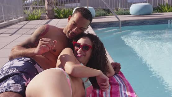 Thumbnail for Black and Hispanic couple laying by pool side together talking laughing smiling holding each other