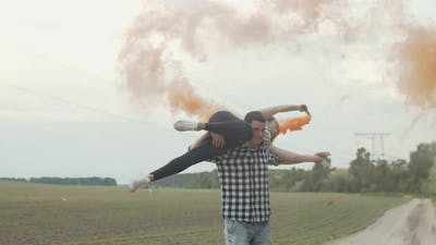 Couple with Colored Smoke Bombs Resting Outdoors