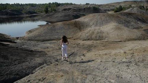 Girl in Sporting White Leggings Runs Through the Sandy Mountain Area