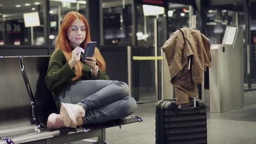 Young Female Uses Phone in Airport Terminal