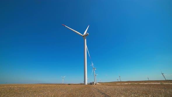 Renewable Wind Power Plant Turbines in a Flat Treeless Brown Field Under Cloudless Clear Sky