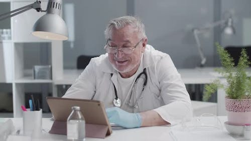A Reliable Male Doctor Leads a Live Broadcast in His Video Blog on a Tablet
