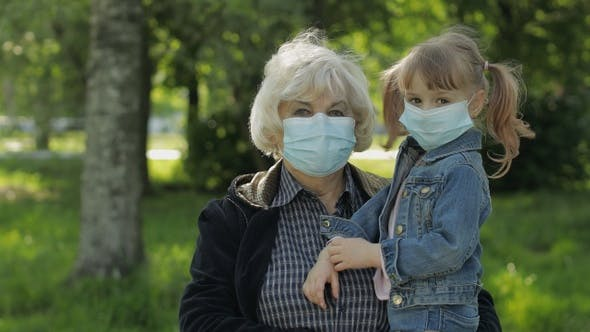 Grandmother with Granddaughter Takes Off Masks After Coronavirus Quarantine End