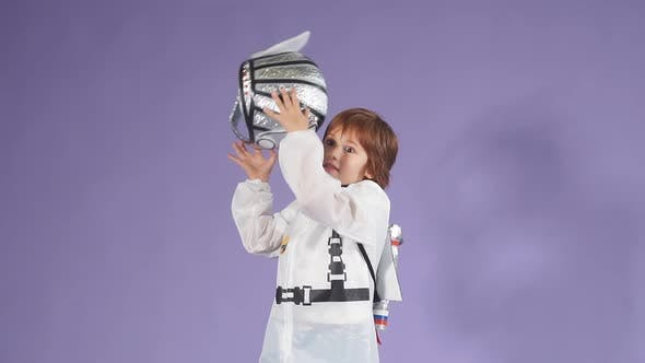 Beautiful Child Dressed in a White Spaceman's Suit and Tossing His Helmet in the Air