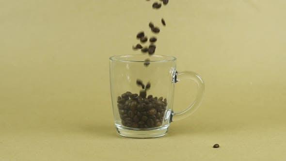 Thumbnail for Kaffeebohnen schnell fliegen, durchsichtiger Glasbecher, beigefarbener Hintergrund. Energie-Konzept