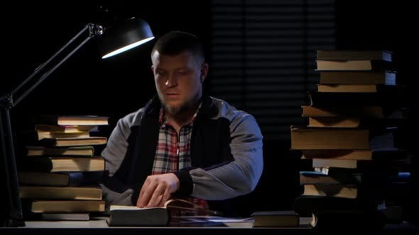 Thumbnail for Guy Comes in and Sits Down at the Table with Books. Black Background