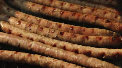 Smoking meat sausages on grill