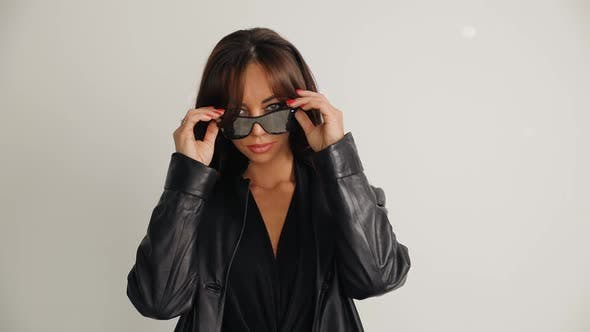 Serious Female Model in Black Taking Off Stylish Sunglasses