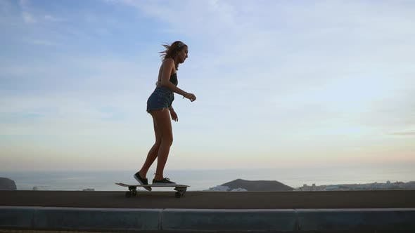 Thumbnail for Girl Riding a Skateboard Near the Ocean and a Large Mountain in Slow Motion