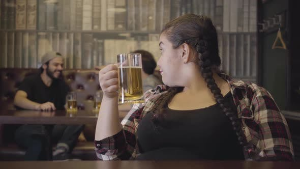 Thumbnail for Plump Woman with Pigtails Sitting at the Bar Counter with a Glass of Beer While Two Men Drinking