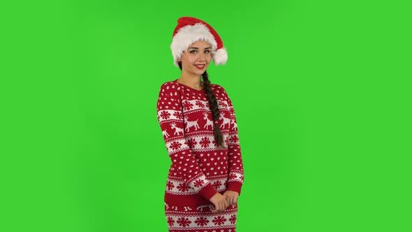 Sweety Girl in Santa Claus Hat Is Smiling and Showing Heart with Fingers Then Blowing Kiss. Green Screen