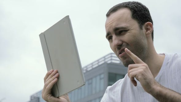 Thumbnail for Young Handsome Man Talking to Someone Using Tablet in A