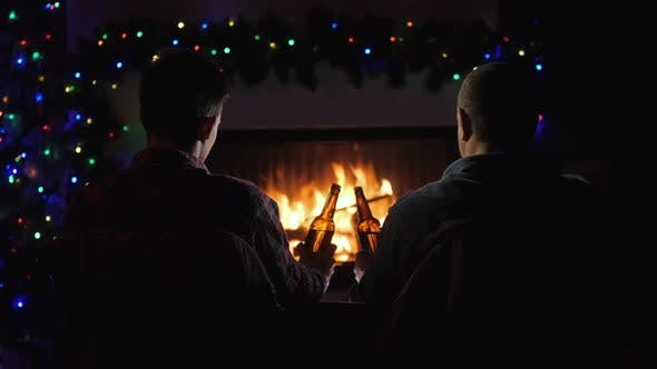 Thumbnail for Two Men Rest with Bottles of Beer in Hand By the Fireplace and Christmas Decorations