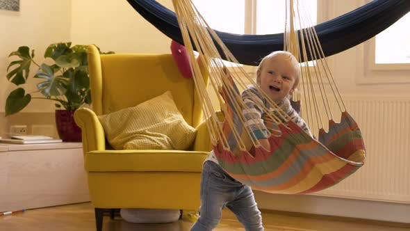 Thumbnail for Adorable infant boy rotating at cushioned single swing.