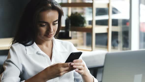 Thumbnail for Young Woman in White Formal Shirt Using Her Phone in Cafe