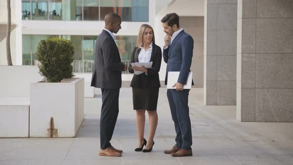 Thumbnail for Young Business Colleagues Discussing Papers Outdoor