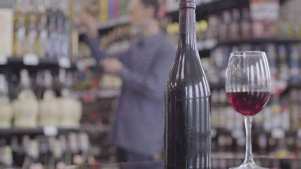Thumbnail for Close-up of Wine Bottle and Wineglass with Beverage Standing at the Foreground with Blurred