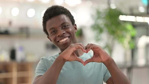 Young African Man Showing Heart Sign with Hand