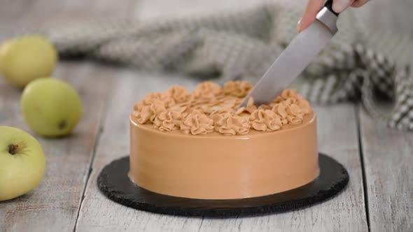 Thumbnail for Female Cutting a Caramel Cake with Almond, on Wooden Table.