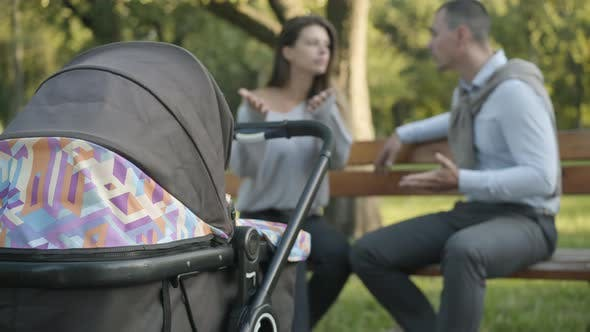 Baby Stroller Standing in Sunny Summer Park with Blurred Couple of Angry Young Parents Arguing at