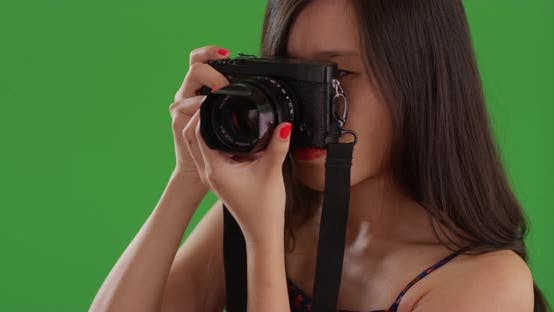Thumbnail for Portrait of young Chinese woman using digital camera on green screen