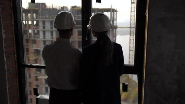 Designers Looking Through Window at Next Building