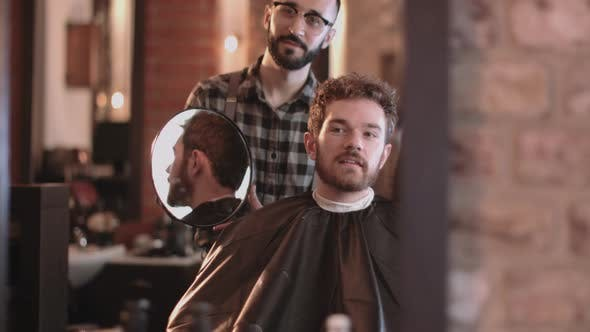 Thumbnail for Barber in hairdresser showing client hair cut