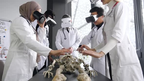 Male and Female Doctors in Hospital Office Studing the Human Skeleton Using Virtual Reality Headset