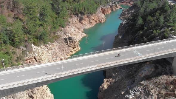 Person is riding on road bicycle on empty bridge over mountain water reservoir