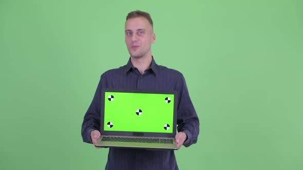 Thumbnail for Happy Handsome Businessman Showing Laptop and Looking Surprised