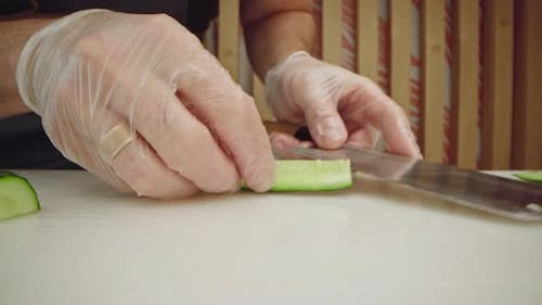 Male Cook Hands in Gloves Cutting Cucumbers on Table Close Up