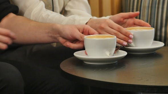 Thumbnail for Hands of man and woman holding cups with coffee