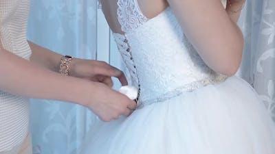 Bride's Bride Helps the Bride Wear a Wedding Dress Closeup