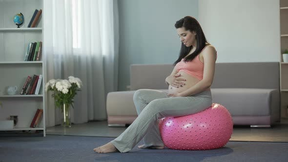 Thumbnail for Young Preggers Lady Listening to Her Baby's Beating, Sitting on Fitness Ball