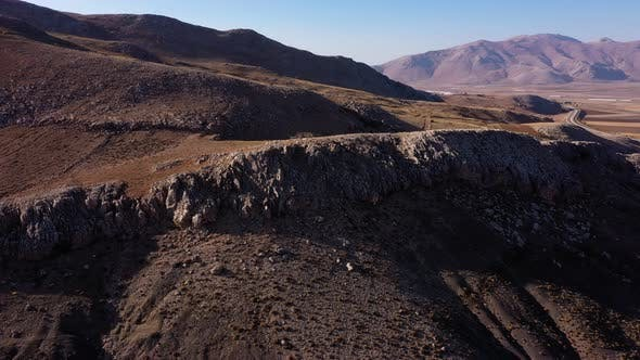 Landscape View of Mountain Valley with Stony Rolling Hills