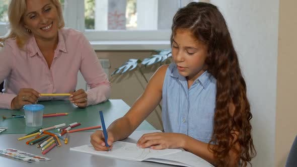 Thumbnail for Adorable Little Girl Drawing While Her Cheerful Teacher Watching Her