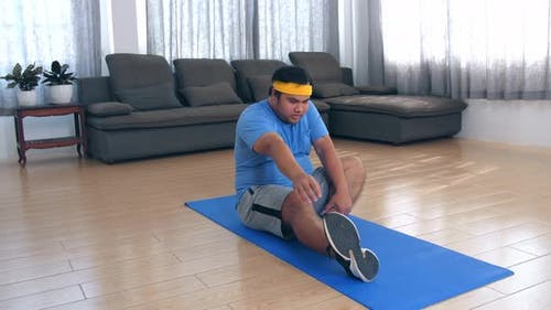 Overweight Man Doing Stretching Exercises At Home