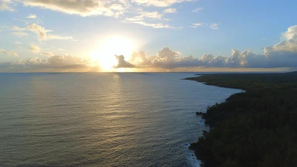 Sunrise Over A Picturesque Coastline with the Sun Rising Over the Sea