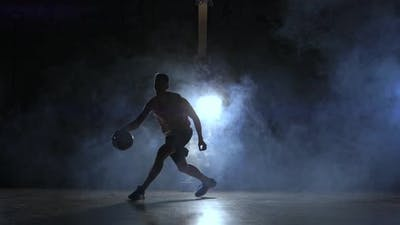 A Man with a Basketball on a Dark Basketball Court Against the Backdrop of a Basketball Ring in the
