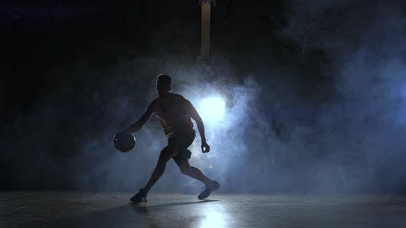 Thumbnail for A Man with a Basketball on a Dark Basketball Court Against the Backdrop of a Basketball Ring in the